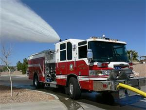 A fire truck parked on a city street spraying water