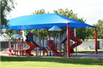 The children&#39s playground - with red slides and a bright blue canopy - at Broadbent Park.
